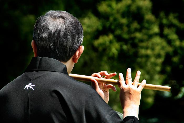 Un flautista japonès, vestit de negre, vist d'esquena