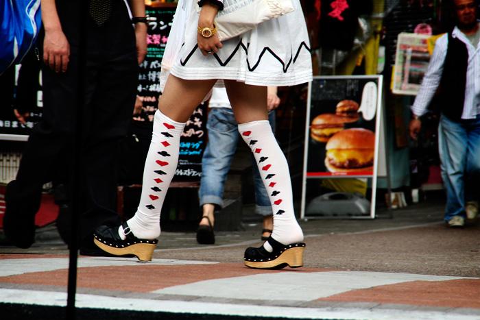 Les cames d'una noia japonesa amb faldilla blanca, esclops i uns mitjons blancs amb cors, trèvols, pics i rombes.