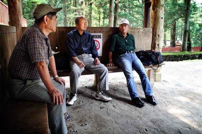 Tres homes japonesos d'uns seixanta anys, un és calb i els altres dos porten gorra, asseguts en un banc de fusta al mig del bosc fent un descans. Se'ls veu molt relaxats.